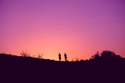 Two young girls silhouettes admire sunset today on hill. Two friends walking in botanical garden against pink lilac purple sky without clouds. Sunset time in city.