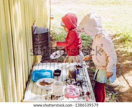 Two young girls sisters play outdoors in so called mud kitchen, where you can make fake food, play with sand, dirt, water, plants and make a mess, it develops imagination and exploration.