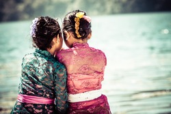 Two young girls sitting close to the lake. Bali. Indonesia