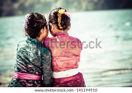 two young girls sitting close...