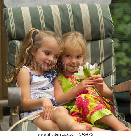 Two young girls sitting in a chair holding a lotus,