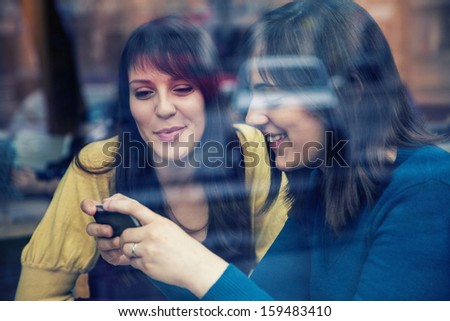Two young girls smiling using smart phone in a cafe The photo was taken through the window