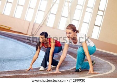 Two young girls sprinting in gym