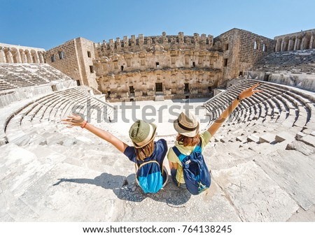Two young girls student traveler enjoy a tour of the ancient Greek amphitheater #764138245