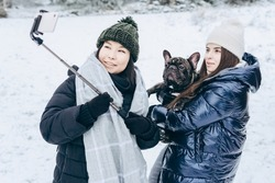 Two young girls take a selfie with their dog against the backdrop of a snowy winter landscape in the open air.Winter lifestyle.Holiday during the Christmas holidays. local travel.healthy break