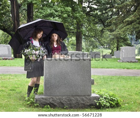 Two young girls visiting a grave site in the rain.  They hold an umbrella, a bouquet of flowers and a teddy bear.