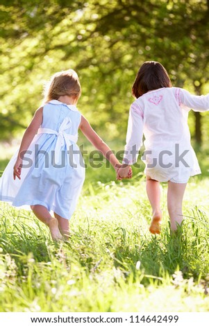 Two Young Girls Walking Through Summer Field Together