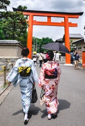Two young girls with kimono walking to the great torii door in the entrance of the Shimagomo Shrine, Kyoto (in the Aoi Matsuri festival celebrations)