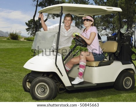 Two young golfers in cart