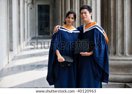 Two young graduates standing in a hallway with their mortar boards