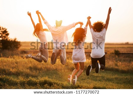 Two young guys and two girls are holding their hand and jumping in the field on a summer day. Back view. #1177270072