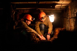 Two young guys in a working uniform and protective helmets, sitting in a low tunnel. Workers of the mine. Miners
