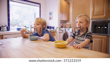 Two young handsome brothers eating cereal together. stock photo