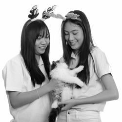 Two young happy Asian teenage girls smiling and holding cat ready for Christmas