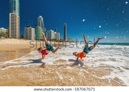 Two young happy boys doing hand stands on Gold Coast beach, Australia #587067071