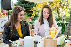 Two young happy brunette women friends in casual clothes having fun and laughing during brunch in cafe outside on sunny day.