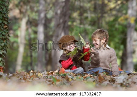 two young happy children - boy and girl - on natural autumn background