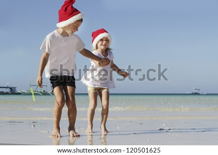 two young happy children in santa hats on tropical beach background - stock photo