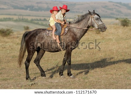 two young happy children riding horse