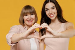 Two young happy daughter mother together couple women wearing casual beige clothes showing close up shape heart with hands heart-shape sign isolated on plain yellow color background studio portrait.