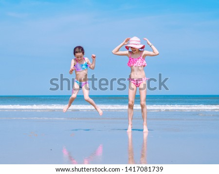 8694afd550779 Two young happy girl having fun on tropical beach and jumping in swimsuit  into the air