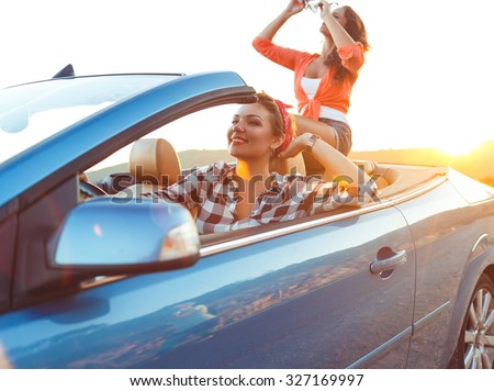 two young happy girls driving a ...