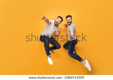 Two young happy men jumping together and pointing away isolated over yellow background #1086914009
