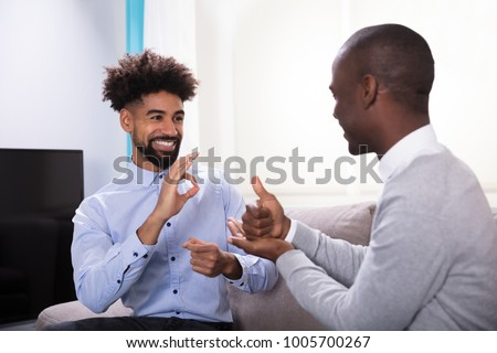 Two Young Happy Men Sitting On The Sofa Making Sign Languages