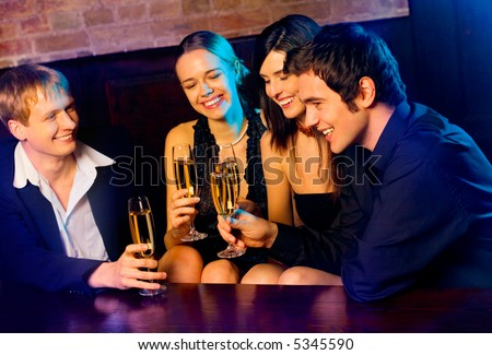 Two young happy smiling couples with champagne glasses at celebration, party or romantic date in night club