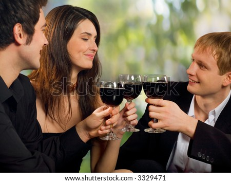 Two young happy smiling men flirting with attractive woman with red-wine, at celebration or party
