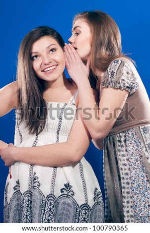 Two young happy teenage girls sharing secrets and laughing on blue background