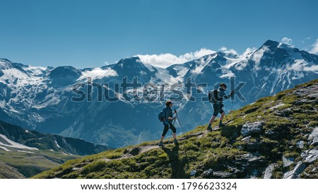 Two young hikers (a couple) walking up a mountain in Austria in summer, with scenic snow covered mountains on the background