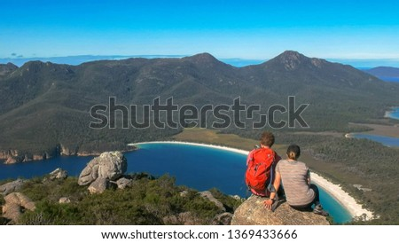 two young hikers enjoy the view of wineglass bay #1369433666
