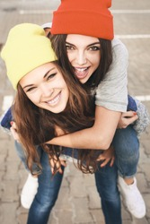 Two young hipster girl friends together having fun. Outdoors, lifestyle.