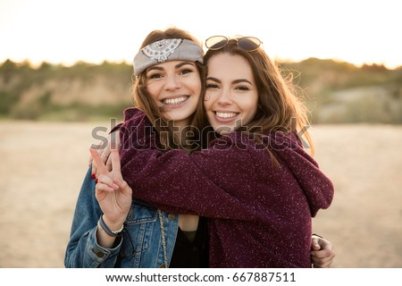 Two young hipster girls embracing each other at the beach