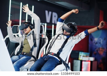 Two young indian people having fun with a new technology of a vr headset at virtual reality simulator.