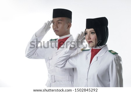 Two young Indonesian National Flag Hoisting Troop salutes, isolated in white. National Paskibraka Council isolated