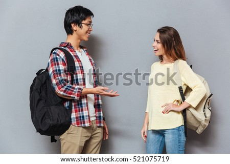 Two young interracial students with backpacks talking isolated on the gray background