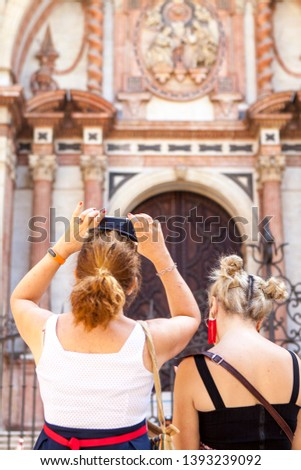 Two young ladies in front of the Catedral of Málaga. Making pictures with mobile phone of the church.