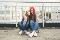 Two young  longboarding girl friends sitting together on long-board and having fun. Outdoors, lifestyle.