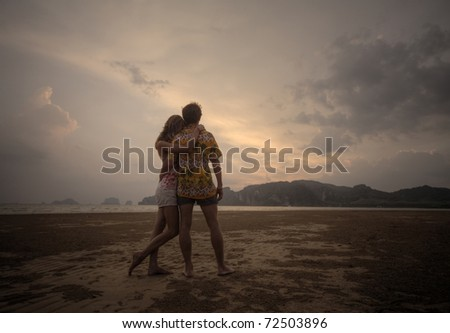 Two young lovers standing on beach and looking to a sunset sky