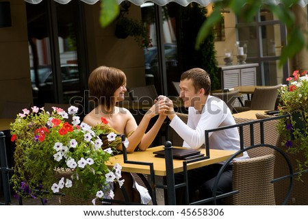 Two young lovers talking at the table