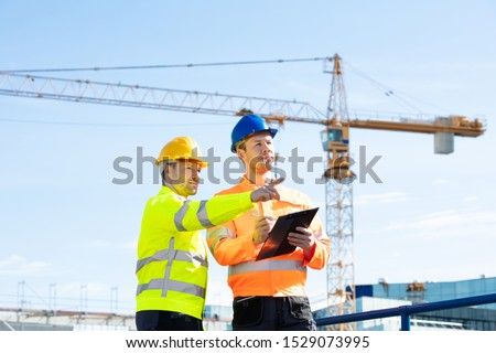 Two Young Male Engineers Standing In Front Of Mechanical Crane Working On The Construction Site