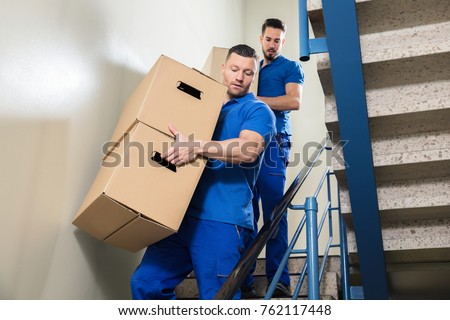 Two Young Male Movers In Blue Uniform Carrying Cardboard Boxes On Staircase #762117448