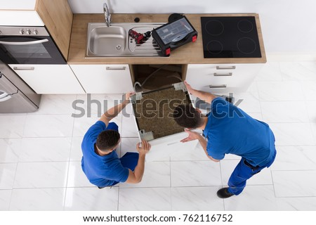 Two Young Male Movers In Uniform Placing Dishwasher In Kitchen