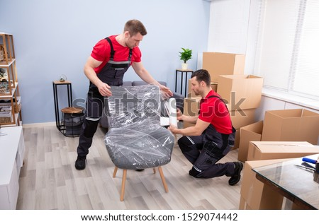 Two Young Male Movers Packing Furniture With Plastic Wrap In Living Room