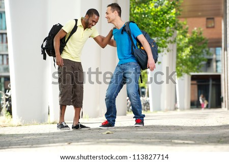 Two young male students walking and laughing outdoors on college campus. Full length portrait of a young African American male student with Caucasian student