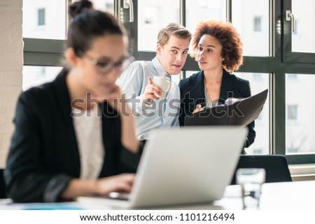 Two young malicious employees gossiping about their hard-working colleague in the office