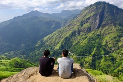 two young man enjoy scenic view of mountain landscape at little adam's peak, sri lanka. back to viewer