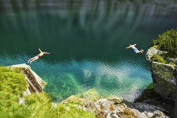 Two young man jumping to the beautiful blue lake in mountains. Summer scenery full of freedom in beautiful landscape